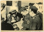 German soldiers going through belongings of Jewish man (Holocaust in Ukraine)