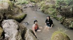 Eleven-year-old Betania sits on a rock next to Prima Sarai in a river in Suchitoto (2011) by Betania Escobar