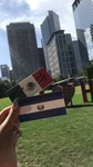Betania holds her Mexican and Salvadoran flags in front of the Houston skyline and the I love Htown installation (2018) by Betania Escobar