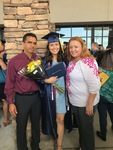 Betania holds yellow flowers and her High School diploma dressed up in a robe and graduation cap with her parents, Jose and Norma, by her side beaming (2018) by Betania Escobar