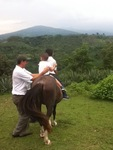 Tio Rene holds his son and Rene on top of a horse (2011) by Betania Escobar