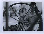 A Woman Sits by a Wagon Wheel