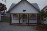 Image of small house next to musuem by Brenda Young, Chris Grasso, and Lori Liggett