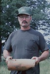Dennis Shinaberry holding drainage tile at his farm by Mark Tebeau