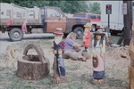 """Brenda Hubbard, carves wood figurines with a chainsaw then works in finer details, the fireman she was working on was going to the """"Chainsaw Auction"""" in which contestants enter the figurines carved with a chainsaw. by Eleanor S. Dahlin"""