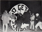 Old photo of players running through a banner